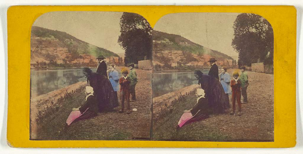[Two women, one man and three children near a river bank]