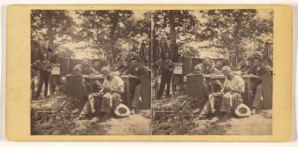 [Group of Civil War soldiers at camp site, one man seated, sewing his shirt]