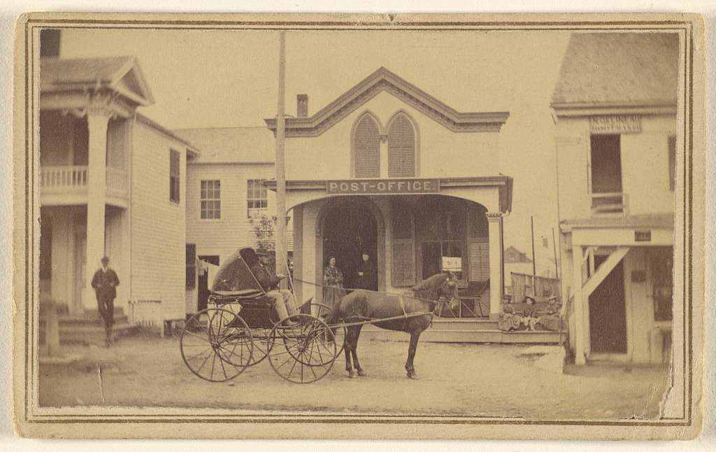 [Man riding horse and buggy in front of post office]