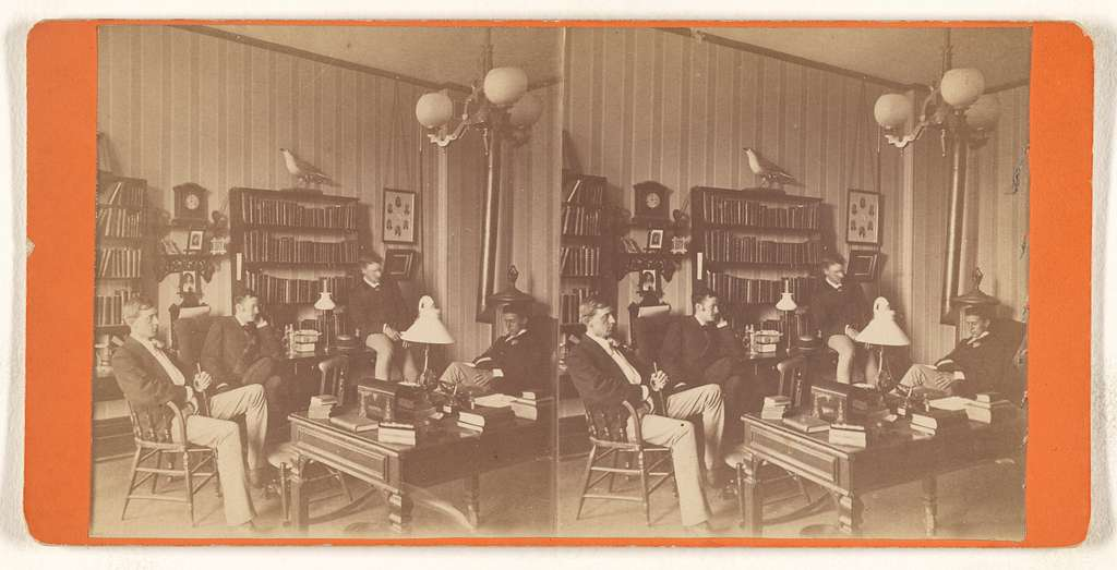 [Four men seated in a study or private library]