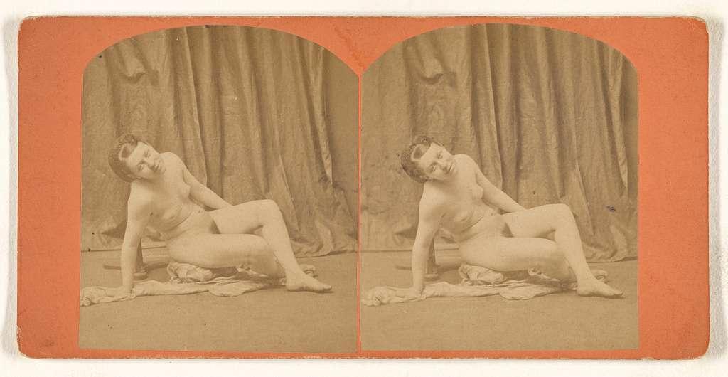 [Nude woman seated on robe on studio floor]