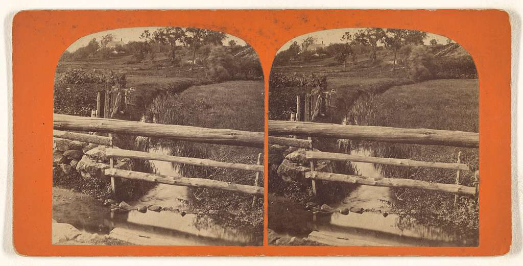 [Small stream between two fields, wooden fence in foreground]