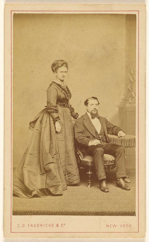 [Unidentified couple: woman standing, man with Vandyke beard seated]