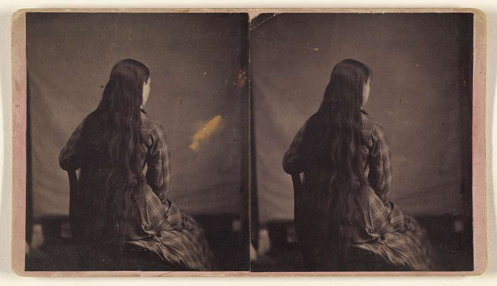 [Woman with extremely long hair seated, back to camera]