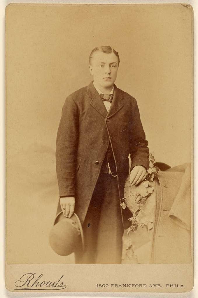 [Man holding derby, standing]